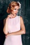 La belle jeune femme avec les cheveux rouges courts dans le rétro style, porte la robe blanche élégante photo libre de droits