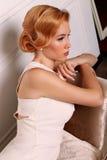 La belle jeune femme avec les cheveux rouges courts dans le rétro style, porte la robe blanche élégante photographie stock