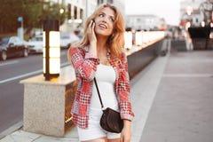La belle jeune femme blonde parle avec l'ami par un téléphone sur la ville de rue Photo libre de droits