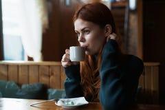 La belle jeune femme boit du thé dans un café, le matin Photo stock