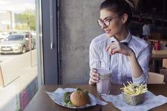 La belle jeune femme caucasienne mangeant des aliments de préparation rapide de déjeuner a fait frire le pot Images libres de droits