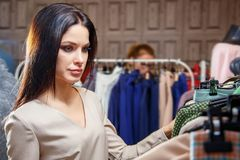 La belle jeune femme choisit la robe dans la boutique Fille sur des achats photographie stock