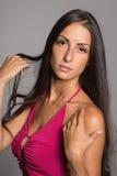 La belle jeune femme corrige des cheveux Image stock