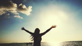 La belle jeune femme court sur la plage tournant autour pendant le coucher du soleil dans le mouvement lent soulevant des bras ap banque de vidéos