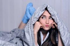 La belle jeune femme couverte par la couverture dans les chaussettes de laine bleues se trouve sur le lit, regarde loin avec les  image stock