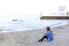 La belle jeune femme détend se reposer sur la plage et apprécie la vue o Photos stock