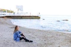 La belle jeune femme détend se reposer sur la plage et apprécie la vue o Image libre de droits