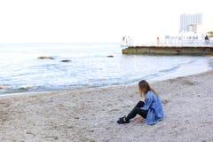 La belle jeune femme détend se reposer sur la plage et apprécie la vue o Photographie stock