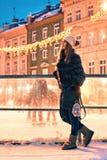 La belle jeune femme dans le manteau de fourrure se tient prêt une frontière de piste de patinage sur le vieux fond européen neig photos stock