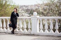La belle jeune femme dans le manteau de laine sombre dans la rue chronomètrent au printemps Fleurs de fleurs d'amande, manteau à  photo libre de droits