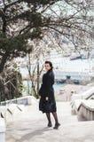 La belle jeune femme dans le manteau de laine sombre dans la rue chronomètrent au printemps Fleurs de fleurs d'amande, manteau à  image stock