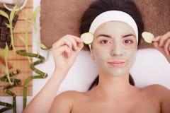 La belle jeune femme dans le masque de boue d'argile sur la bâche de visage observe avec le concombre de tranches Photo stock