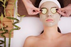 La belle jeune femme dans le masque de boue d'argile sur la bâche de visage observe avec le concombre de tranches Photos libres de droits