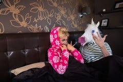 La belle jeune femme dans le pyjama se trouve sur le lit avec l'ami étrange Photographie stock libre de droits