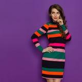 La belle jeune femme dans la robe vibrante semble partie et pensée photo stock