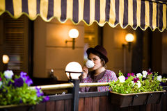 La belle jeune femme dans un chapeau s'assied sur une terrasse dans un café, boit du thé et regarde l'appareil-photo photo stock