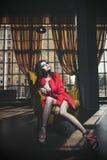 La belle jeune femme dans un manteau de corail et des espadrilles s'assied dessus Images stock