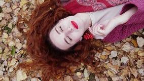 La belle jeune femme de détente avec les cheveux rouges se trouve au-dessus des feuilles sèches dans la forêt d'automne Photographie stock libre de droits