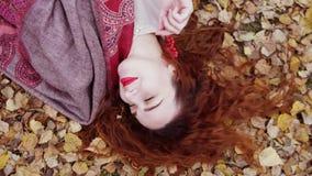 La belle jeune femme de détente avec les cheveux rouges se trouve au-dessus des feuilles sèches dans la forêt d'automne Photographie stock