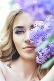 La belle jeune femme de mode extérieure entourée par le lilas fleurit l'été Buisson lilas de fleur de ressort Portrait d'une fill Image libre de droits