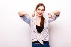 La belle jeune femme de sourire heureuse montrant des pouces font des gestes vers le bas Images stock