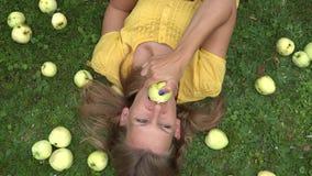 La belle jeune femme de sourire se trouvant sur l'herbe et le peu goûtent le fruit de pomme 4K banque de vidéos
