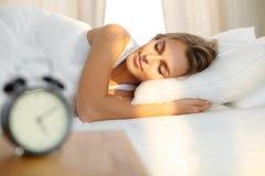 La belle jeune femme dormant tout en se situant dans le lit confortablement et avec bonheur Sunbeam naissent sur son visage photographie stock