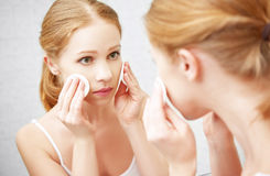 La belle jeune femme enlève le maquillage avec la peau de visage dans le mirro Image libre de droits