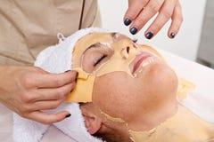 La belle jeune femme enlèvent le masque facial à un centre de beauté Images stock