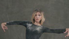 La belle jeune femme exécutent la danse moderne dans le studio sur le fond gris avec de éclabousse la poudre ou la poussière blan banque de vidéos