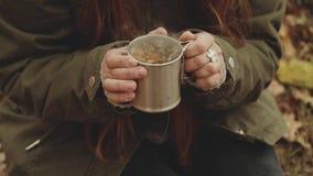 La belle jeune femme heureuse boit du thé chaud près du feu de camp dans la forêt d'automne, plan rapproché, feuilles de chêne, p banque de vidéos