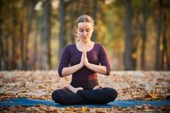 La belle jeune femme médite dans l'asana Padmasana de yoga - la pose de Lotus sur la plate-forme en bois en parc d'automne image libre de droits