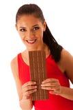 La belle jeune femme mange du chocolat d'isolement au-dessus du backgro blanc Image stock