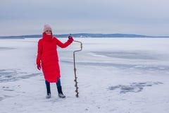 La belle jeune femme mignonne avec la perceuse de glace se tient sur la rivière congelée et se prépare à la pêche images libres de droits