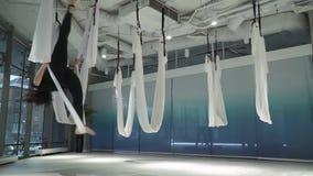 La belle jeune femme plane dans l'hamac dans l'espace aérien du studio à l'intérieur banque de vidéos