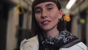 La belle jeune femme regardant la caméra dans le tram, les cheveux de réparation et souriant, steadicam a tiré Plan rapproch? banque de vidéos
