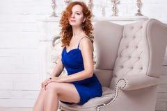 La belle jeune femme rousse dans une robe bleue s'assied dans une chaise Photos stock