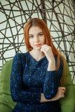 La belle jeune femme s'assied dans une chaise pendante dans la chambre Photo libre de droits
