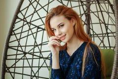 La belle jeune femme s'assied dans une chaise pendante dans la chambre Photo stock