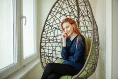La belle jeune femme s'assied dans une chaise pendante dans la chambre Image libre de droits