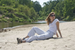 La belle jeune femme s'assied sur la plage sablonneuse Images stock