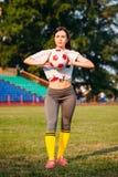 La belle jeune femme sportive dans les vêtements de sport s'exerce dans le stade avec la boule du football Tenir la boule image stock