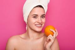 La belle jeune femme veut manger l'orange avec la serviette enroulée autour de la tête et des épaules nacked Le modèle de sourire images libres de droits