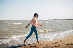 La belle jeune fille avec les cheveux noirs dans une chemise et des jeans a l'amusement sur la plage de la mer d'Azov Photographie stock libre de droits