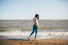 La belle jeune fille avec les cheveux noirs dans une chemise et des jeans a l'amusement sur la plage de la mer d'Azov Images libres de droits