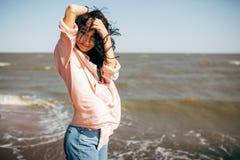 La belle jeune fille avec les cheveux noirs dans une chemise et des jeans a l'amusement sur la plage de la mer d'Azov Image stock