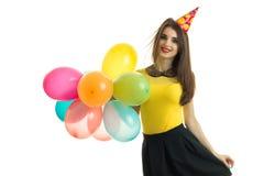 La belle jeune fille avec un chemisier lumineux et des ballons colorés regarde le kaeru et le sourire Photos stock