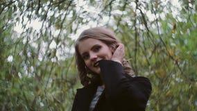 La belle jeune fille blonde élégante pose pour l'appareil-photo sur un fond des feuilles d'arbre, mouvement lent clips vidéos