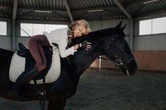 La belle jeune fille blonde élégante se trouve sur une sa chemise blanche de chemisier de cheval de habillage de concurrence noir Image libre de droits