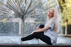 La belle jeune fille blonde avec un joli visage et un beau sourire observe Le portrait d'une femme avec de longs cheveux et stupé Photos libres de droits